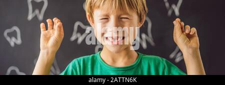 Il ragazzo caucasico little tiene un dente di latte caduto fra le sue dita e ride guardando nella BANDIERA della macchina fotografica, FORMATO LUNGO Foto Stock