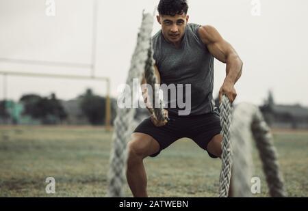 Giovane uomo muscoloso che lavora fuori con corde di battaglia. Misura il giovane atleta maschio che fa l'allenamento della corda di battaglia all'aperto su un campo.