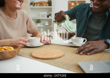 Primo piano di giovani coppie multietniche che si godono l'un l'altro e bere caffè al tavolo nella cucina domestica Foto Stock