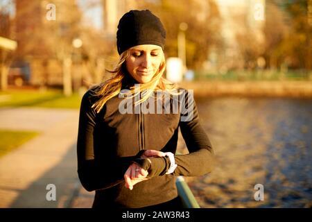 Una donna atletica che controlla le statistiche di corsa sul suo orologio intelligente. Foto Stock