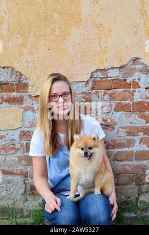 Ragazza giovane, cute accanto porta che indossa occhiali rossi, jeans e t-shirt, posando con il suo animale domestico di fronte a grunge muro di mattoni