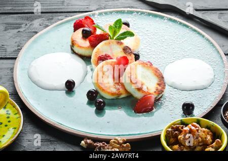 Frittelle di formaggio con fragole e panna acida. Colazione. Nella piastra. Vista dall'alto. Composizione a disposizione piatta spazio di copia libero.