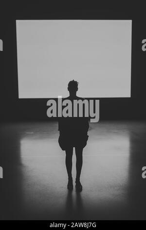 Spettacolare immagine in bianco e nero di una Silhouette di una figura umana femminile in piedi con retro alla telecamera con uno schermo illuminato sullo sfondo