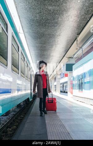 Donna elegante che va per un viaggio d'affari in treno