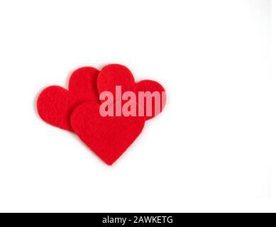 Cuori tessili rossi su sfondo bianco. Concetto di giorno di San Valentino. Spazio di copia, vista dall'alto, disposizione piatta. Foto Stock