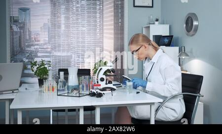 Nel laboratorio di chimica moderna, lo scienziato di ricerca femminile che utilizza la pipetta per far cadere i fertilizzanti sul cursore e poi esaminarlo sotto una lente di ingrandimento Foto Stock