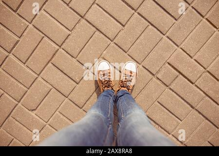 Vista dall'alto delle gambe della ragazza in gomshoes e jeans sul marciapiede Foto Stock