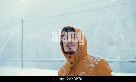 Ritratto di un uomo freddo che indossa un cappotto che ha preso nevicata nel freddo nella neve. Concetto invernale. Foto Stock