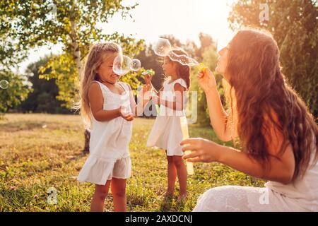 Giorno della madre. Donna aiuta le figlie a soffiare bolle di sapone nel parco estivo. Bambini che giocano all'aperto