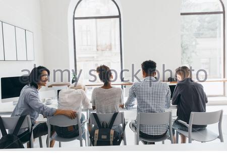 Ragazza stanca in camicia bianca seduta tra uomo asiatico e donna africana durante la riunione di lavoro. Ritratto al coperto dal retro dello studente asiatico e dei suoi amici che si rilassano nella sala universitaria dopo la lezione. Foto Stock