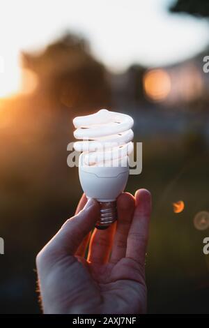 Lampada fluorescente tenuta da una persona all'esterno. Inquadratura dal punto di vista. Concetto Di Economia. Foto Stock