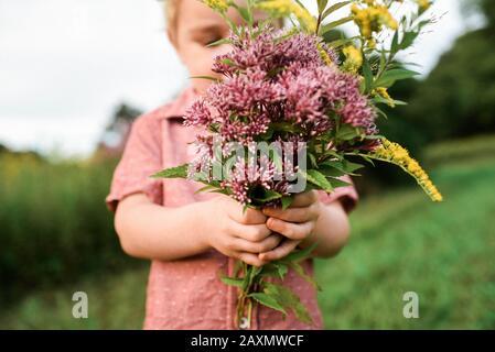 Piccolo bambino che tiene un bouquet di fiori selvatici che ha scelto. Foto Stock