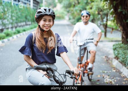 le coppie asiatiche giovani indossano i caschi godono di bici da corsa insieme sui viaggi nel parco Foto Stock