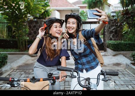Due giovani asiatici donna che indossa il casco e sacchetti con fotocamera cellulare fare un contenuto video sulla bicicletta pieghevole prima di andare al campus Foto Stock