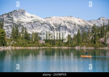 Vista laterale del paddle board donna attiva sul lago di montagna. Foto Stock