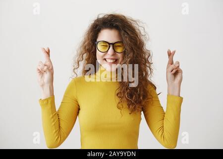 Donna emozionata in maglione giallo mantenendo le dita incrociate, bocca aperta, in attesa di momento speciale isolato su sfondo grigio Foto Stock