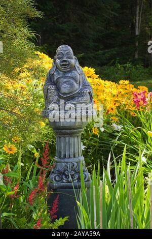 Statua di Buddha in cemento sulla cima di una colonna al confine con rosso Astilbe 'raggio' e giallo Rudbeckia - Coneflowers in giardino cortile Country in estate Foto Stock