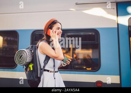Tema turismo e viaggi giovane studente. Bella giovane caucasica ragazza in abito e cappello in piedi alla stazione ferroviaria vicino wit treno