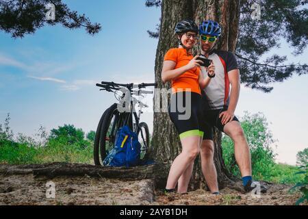 Coppia felice alla ricerca sulla mappa in una destinazione smartphone. Uomo e donna in caschi che viaggiano in mountain bike su terreni accidentati. Foto Stock