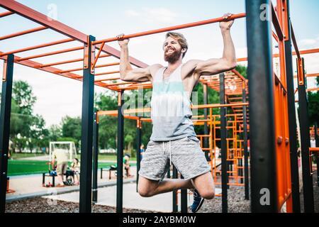 atleta forte che fa pull-up su barra orizzontale. Uomo muscoloso che fa tirare su barra orizzontale in parcheggio. Palestra Durante Il Lavoro Foto Stock