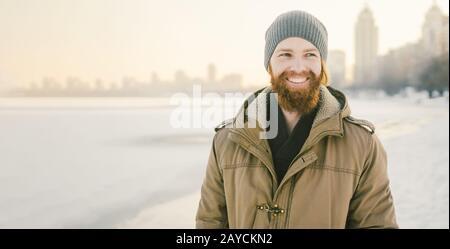 Primo piano giovane caucasico capelli rossi maschio e barba in un cappello e un cappotto parco che posa modello invernale contro uno sfondo di un lago a. Foto Stock