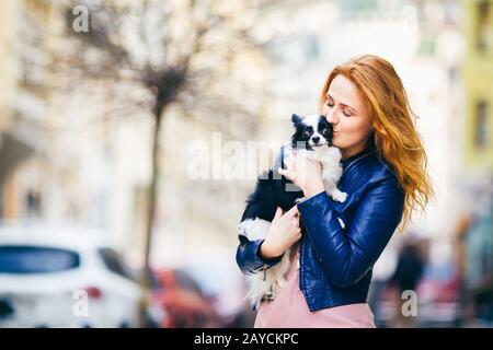 Una giovane donna caucasica dai capelli rossi con le prese e i baci dei fregi, abbracciando il cane shaggy bianco e nero della razza Chihuahua. Ragazza Foto Stock