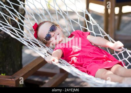 Adorabile bambina sulla vacanza tropicale rilassandovi in amaca Foto Stock
