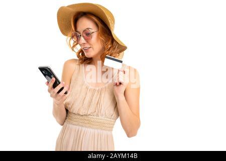 carino turista in un cappello vestito in un abito estivo e occhiali da sole ordini biglietti per telefono e tiene una carta di credito con un mockup su uno sfondo bianco spirito
