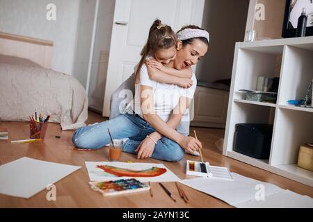 divertente bambina che inframa sua madre mentre sta dipingendo una foto sul pavimento, donna eccitata con ampia bocca aperta sta aiutando sua figlia a fare Foto Stock