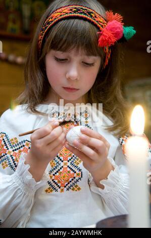 Ivano-Frankivsk Oblast/Ucraina - 10.07.2008. La ragazza vestita con costumi folk ucraini dipinge le uova per Pasqua.