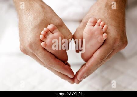 In prossimità delle mani dell'uomo tiene il suo bimbo di piedi e creazione di forma di cuore. Foto Stock