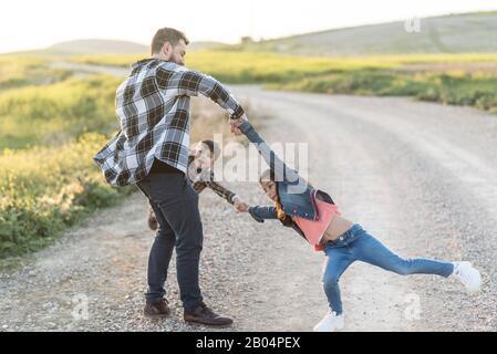 Padre che circling in aria i suoi figli, che sono sospesi giocare all'aperto felice Foto Stock
