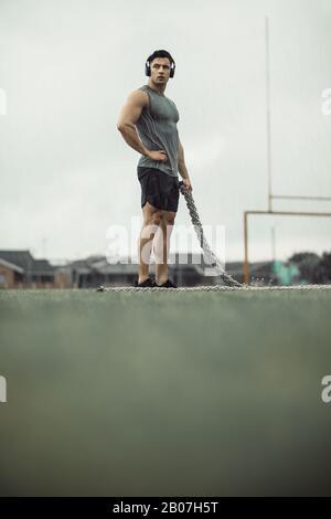 Giovane forte che si trova sul campo con una corda da battaglia e guarda lontano. Sportivo che si prende pausa dalla corda di battaglia allenamento all'aperto.