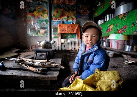 Il bambino tibetano siede alla stufa. Nei giorni freddi, i tibetani si ritirano nelle loro case e si siedono vicino alla stufa per rimanere caldi Foto Stock