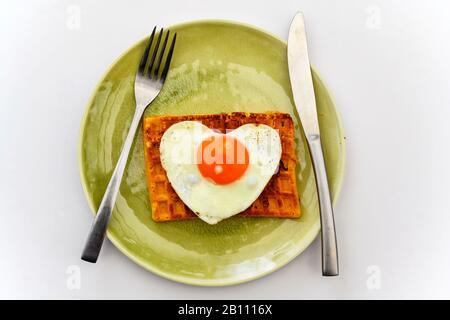 Uovo fritto a forma di cuore su waffle tostati