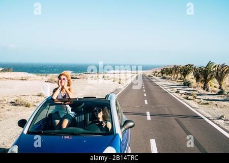 Viaggia con gli amici e viaggia con l'auto blu convertibile e un paio di amici adulti donne divertirsi insieme guidare su una lunga strada con l'oceano in backgr