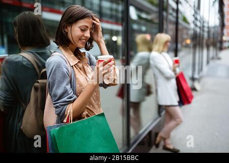 Felice giovane donna bere togliere il caffè e camminare con le borse dopo lo shopping in città. Foto Stock