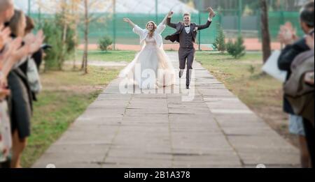 primo piano. felice sposa e sposo che corrono lungo la strada della città. Foto Stock