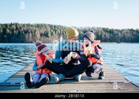 papà sedette su un molo in una muta mangiando frutta con i suoi bambini in spiaggia