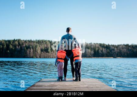 padre e i suoi figli in piedi alla fine di un molo che guarda al mare Foto Stock