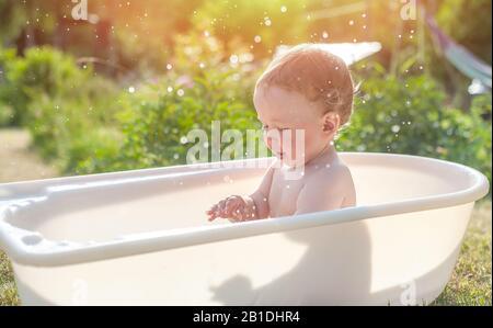 Il bambino si lava nel bagno sull'erba verde. Piccolo bambino che si diverte, spruzzi d'acqua e ride. Felice bambino che fa il bagno all'aperto sull'erba verde dentro Foto Stock