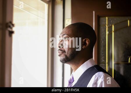 Un ritratto di un uomo afro-americano che guarda all'aria aperta a casa