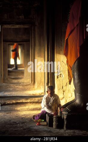 Angkor Wat Interno. Donna che mette offerte agli dei. Grandi statue di Vishnu vestite di tessuto arancione. Dawn,