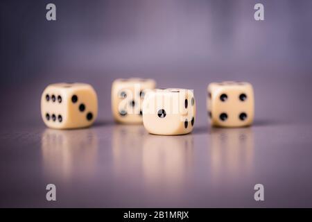 Quattro dadi su sfondo grigio viola, spazio di copia Foto Stock