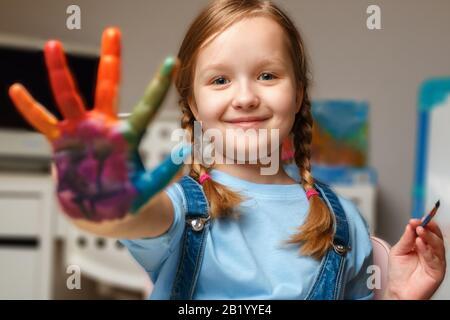 Bellissima bambina con le mani nella vernice. Il bambino disegna al tavolo. Foto Stock