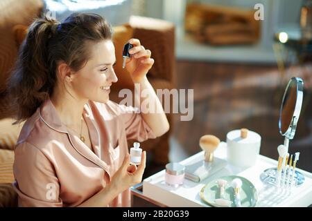 felice donna elegante in pigiama utilizzando elisir cosmetico vicino al tavolo con prodotti da bagno a casa moderna nella soleggiata giornata invernale. Foto Stock