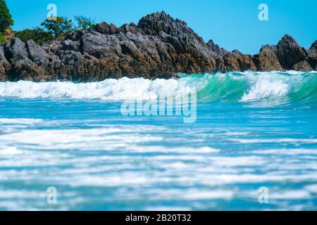 Curling e rottura onda in surf con rocce scoscese dietro al bMount Maunganui, Tauranga, Nuova Zelanda.