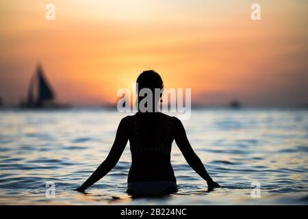 Silhouette di una ragazza che ammira un tramonto mozzafiato sulla spiaggia bianca di Boracay. La Spiaggia Bianca di Boracay si trova alla Stazione 1. Foto Stock