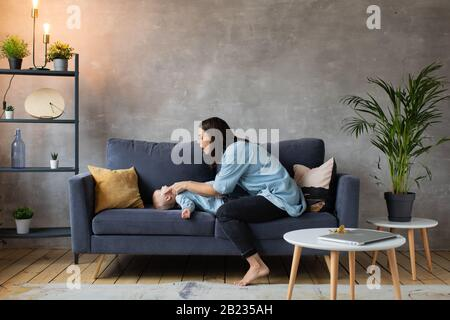 Young Mother Playing with Children on the Couch. Happy Family. Comfort della casa.