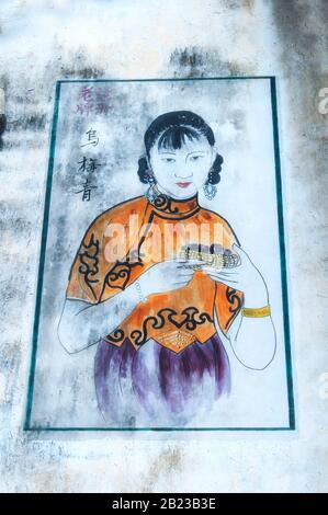 Wuzhen, Cina. 29 Agosto 2015. Un dipinto di una donna cinese del 19th secolo indossando un abito tradizionale in stile cheongsam su una parete all'interno del Foto Stock